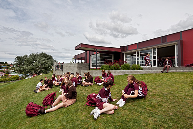 Ogilvie High School Student Centre, students sitting outside on grass